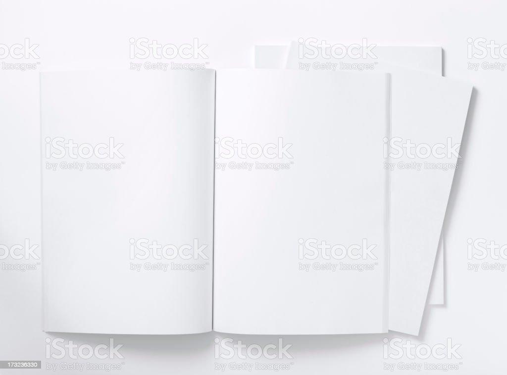Blank white magazine lying open on a white table stock photo