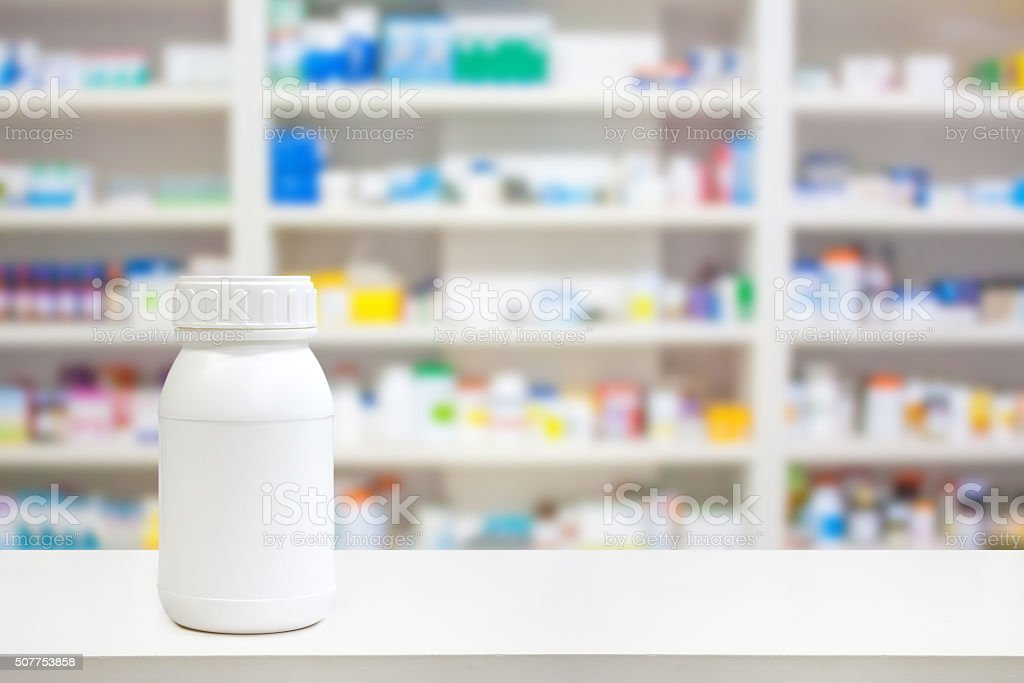 Blank white medicine bottle on counter with pharmacy drugstore stock photo