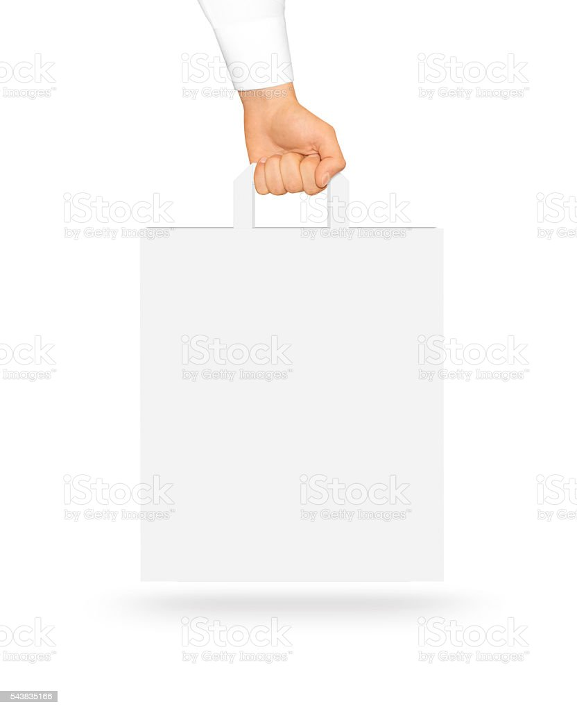 Blank white paper bag mock up holding in hand. Empty stock photo