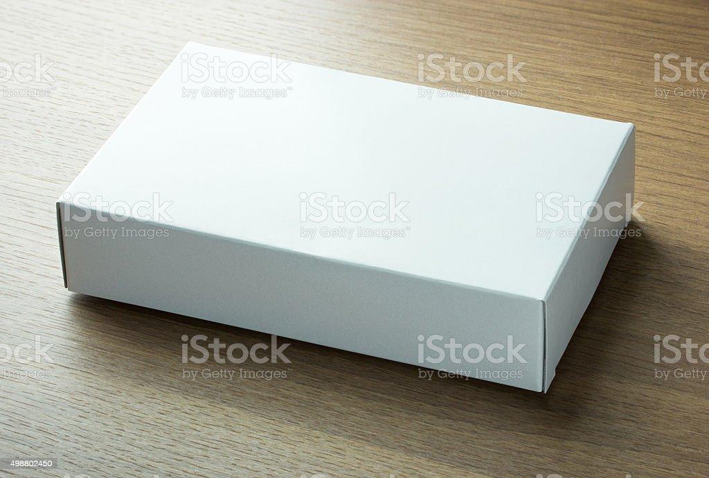 blank white paper box on dark wood background stock photo