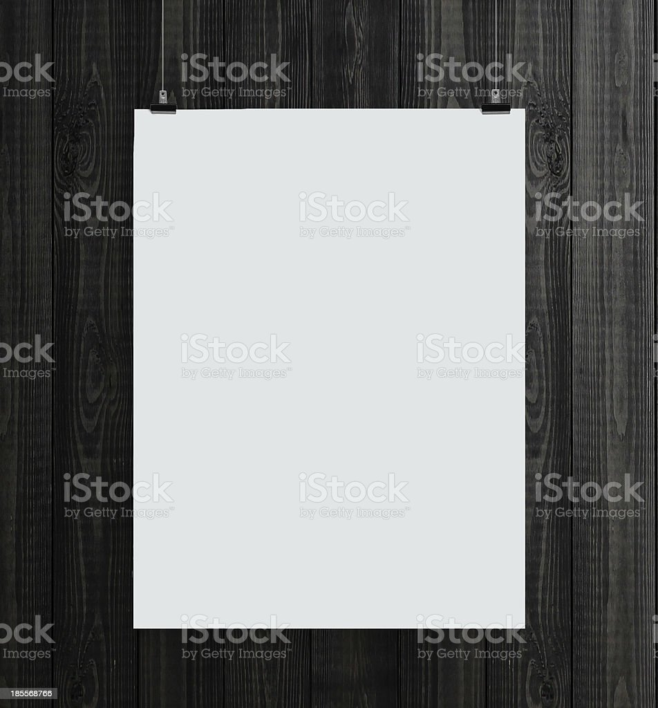 Blank white paper card hanging in front of a wooden backdrop royalty-free stock photo