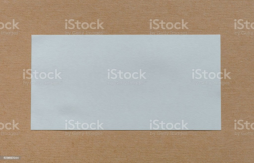 Blank white paper label on cardboad background stock photo