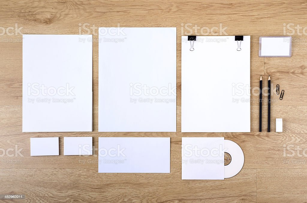 Blank white paper of various sizes on a wooden desk royalty-free stock photo