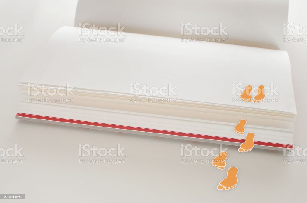 Blank white paper open book on white background with footstep stock photo