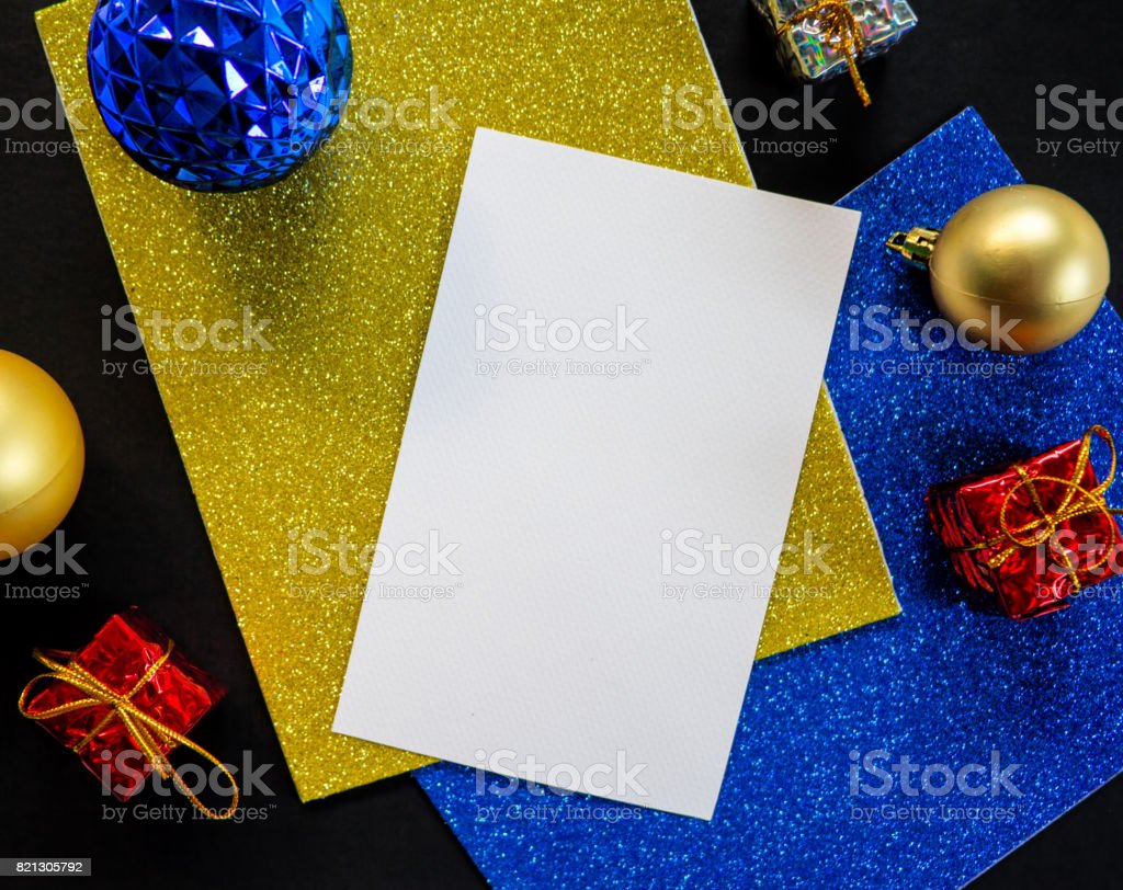 Blank white paper with Christmas ornament and glitter. Christmas tree ornament on the table. stock photo