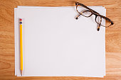 Blank, white papers on wooden desk. Eyeglasses, pencil.