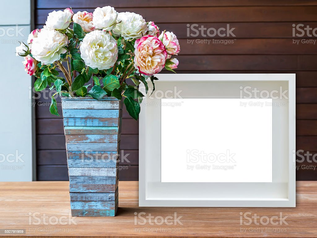 Blank white picture frame and flowers vase on wooden desktop stock photo