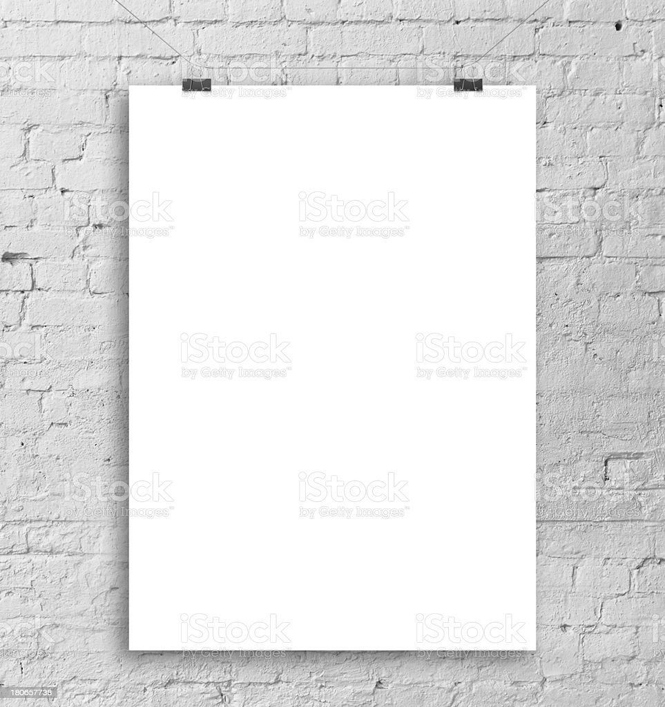 A blank white poster in front of a grey brick wall stock photo