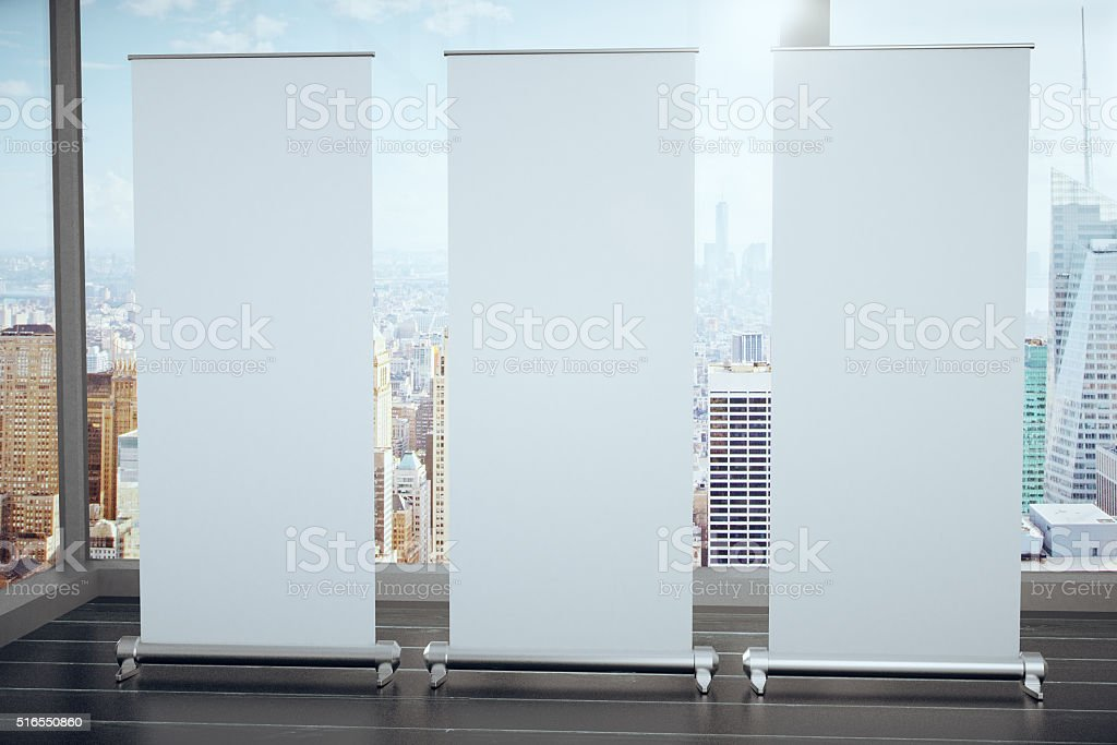 Blank white posters on black wooden floor and glassy walls stock photo