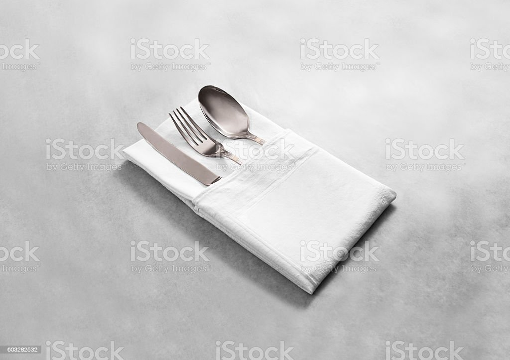 Blank white restaurant cloth napkin mock up with silver cutlery stock photo
