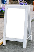 Blank white signboard stand on storefront.