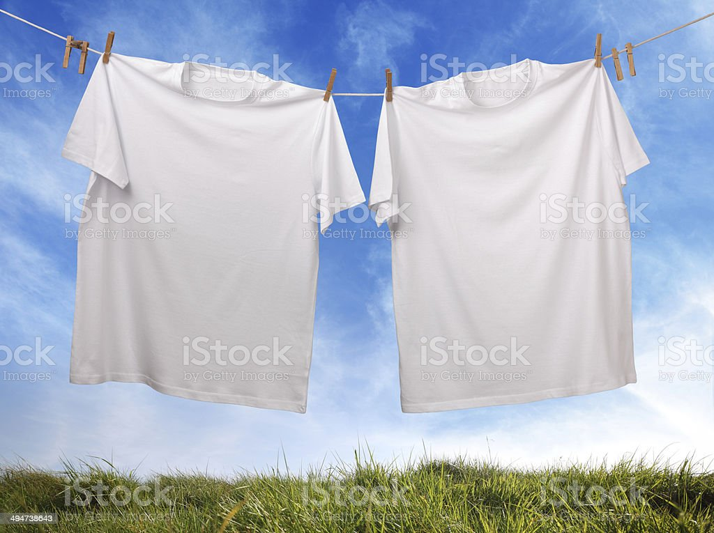 Blank white t-shirt hanging on clothesline stock photo