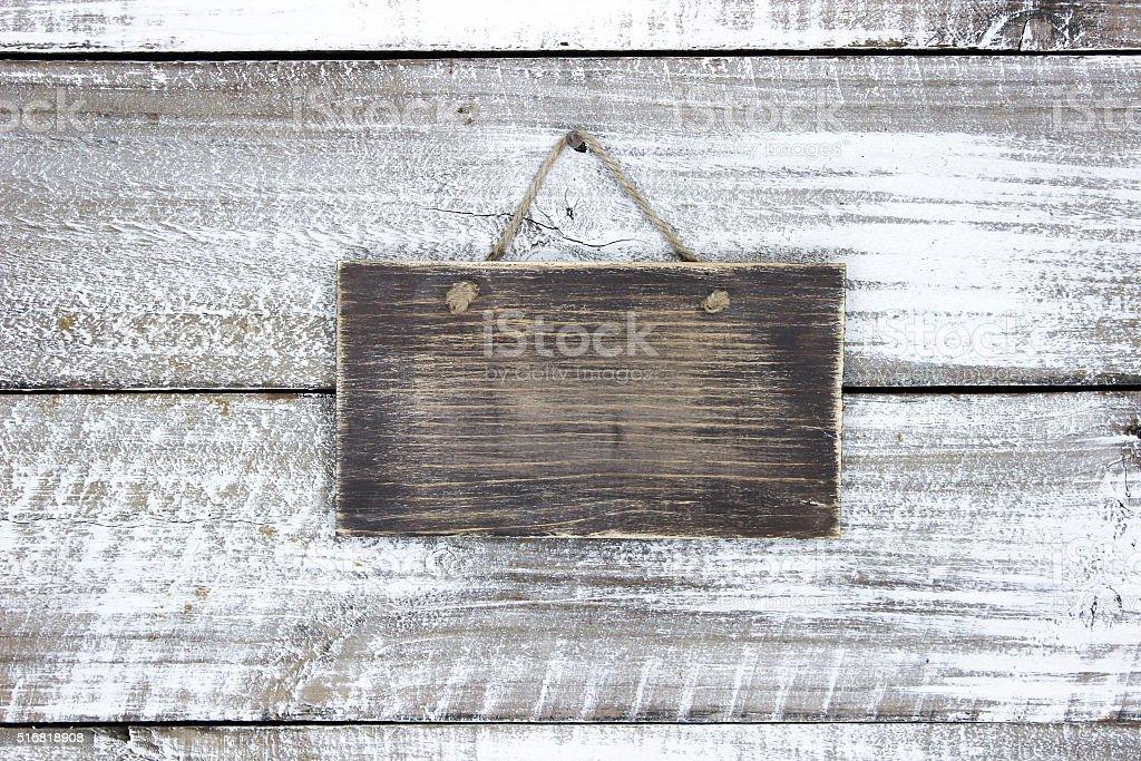 Blank wood sign hanging on rustic door stock photo