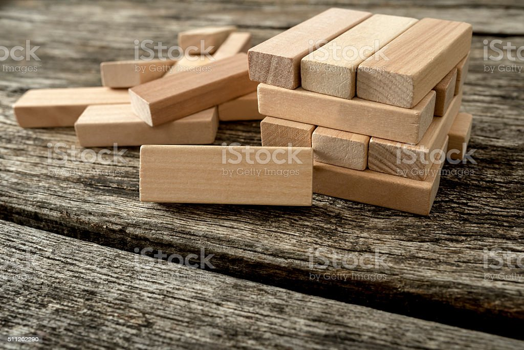 Blank wooden block leaning on structure made of other blocks stock photo