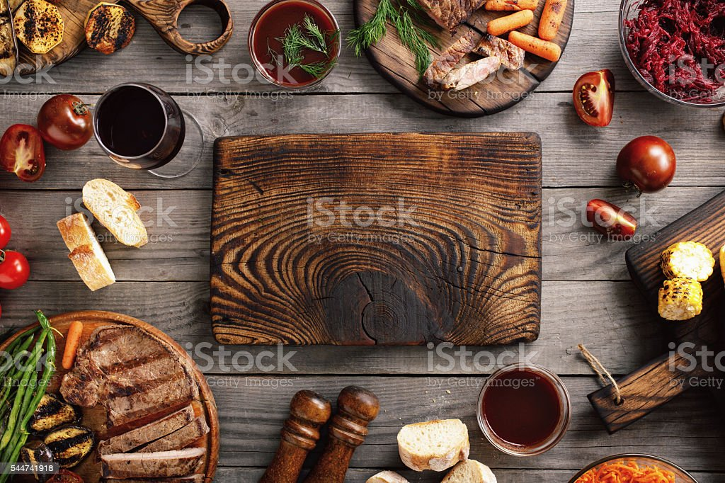 Blank wooden cutting board with succulent steaks and grilled veg stock photo