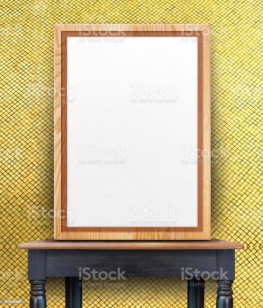 Blank wooden photo frame leaning at gold mosaic tile wall stock photo