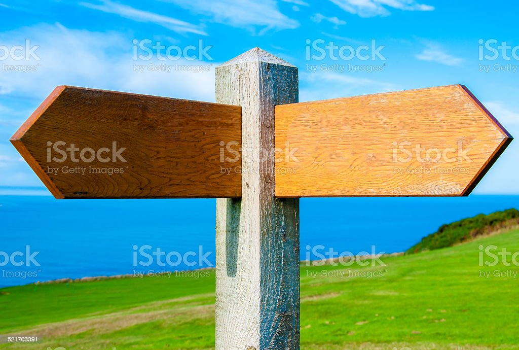 Blank wooden signpost with two arrows over clear blue sky stock photo