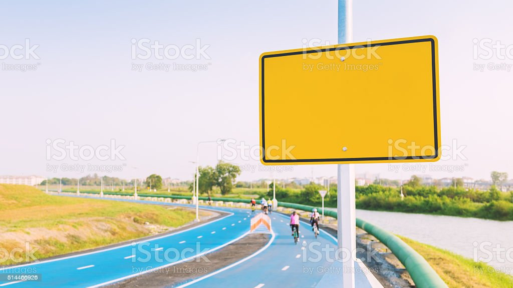 Blank yellow billboard on bike lane (vintage tone). stock photo
