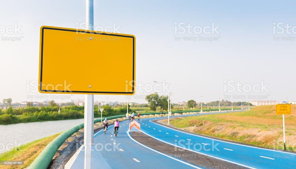 Blank yellow billboard on bike lane. stock photo