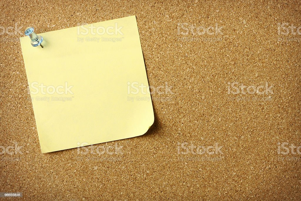 Blank yellow note on cork message board stock photo