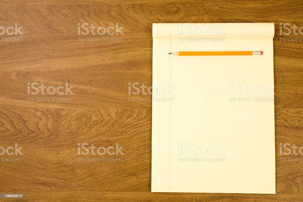 Blank yellow notepad on desk with pencil. stock photo