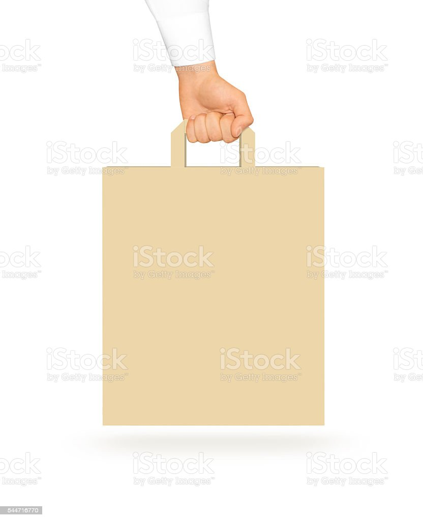 Blank yellow paper bag mock up holding in hand. Empty stock photo