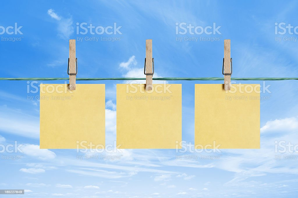 Blank yellow post it notes drying on a clothes line stock photo