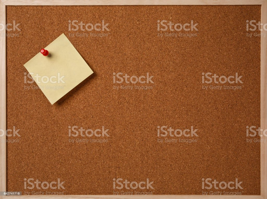 Blank yellow sticky note pinned on a cork bulletin board stock photo