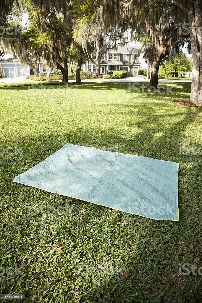 Blanket on grass, houses in background stock photo