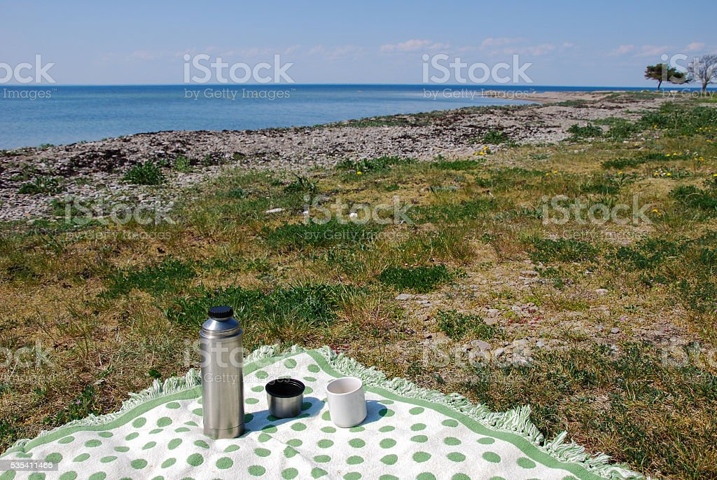 Blanket with thermos on the beach stock photo
