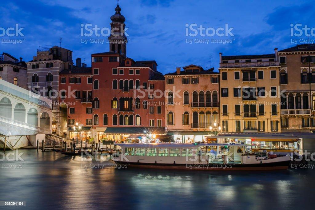 Blaue Stunde am Canal Grande, Fahrgastschiff, Botsanleger und bunte Häuser stock photo
