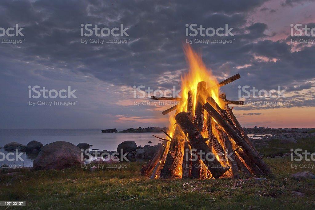 Blazing bonfire near a body of water at dusk stock photo