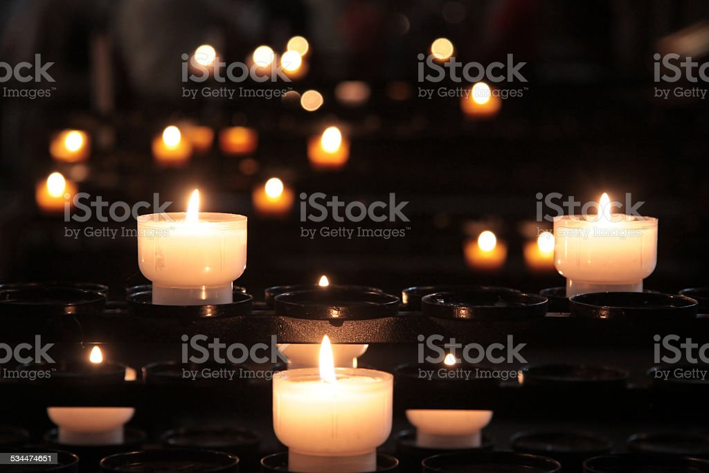 Blazing candle-flames in church stock photo