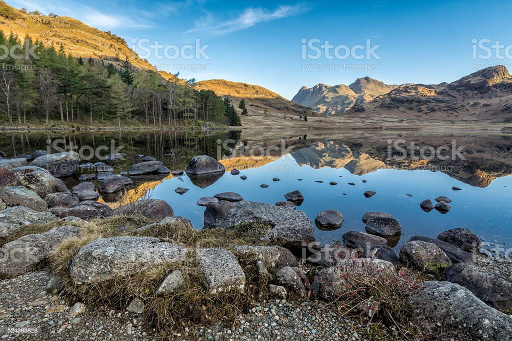 Blea Tarn With Rocks In Foreground And Clear Reflections. stock photo