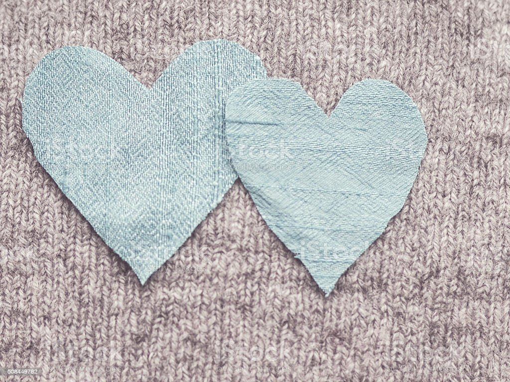 Bleached image of blue silk hearts overlapping on grey knit stock photo
