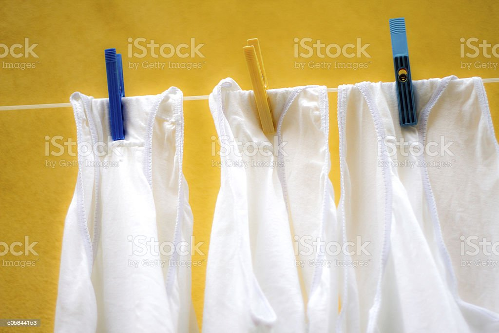 Bleached White Panties on Line Against Yellow Italian Wall stock photo