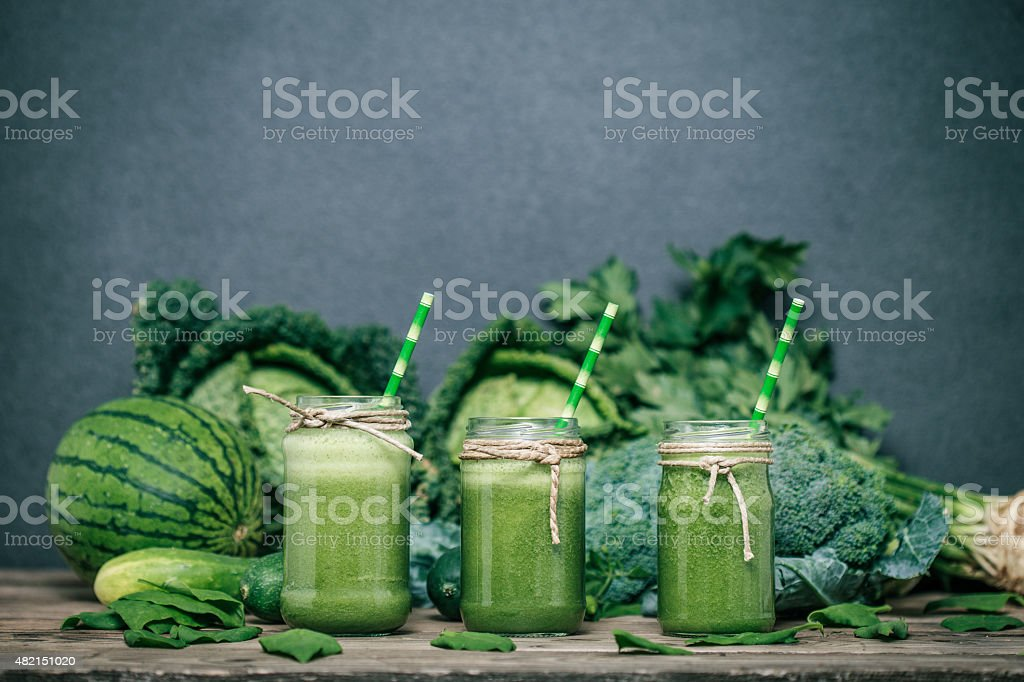 Blended green smoothie with ingredients on wooden table stock photo