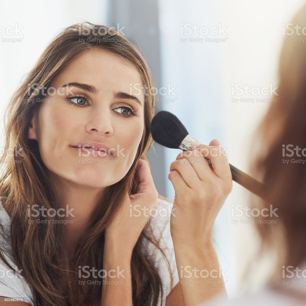 Blending her makeup for a natural look stock photo