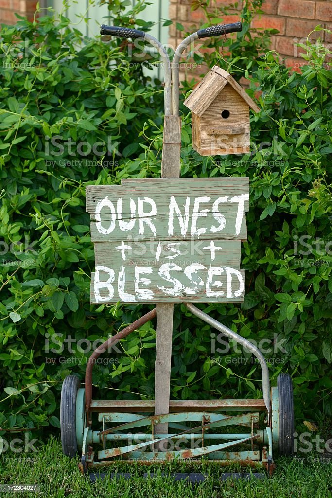 Blessed Nest: old push mower with sign and birdhouse stock photo
