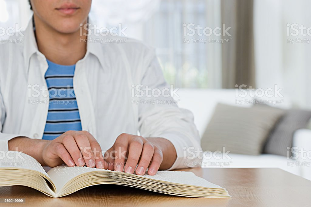 Blind boy reading a braille book stock photo