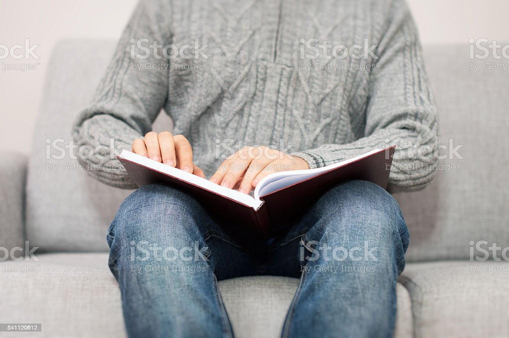 Blind man reading braille book on the couch. stock photo