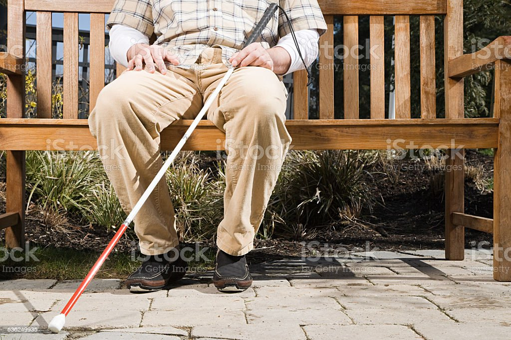 Blind man sitting on a bench stock photo