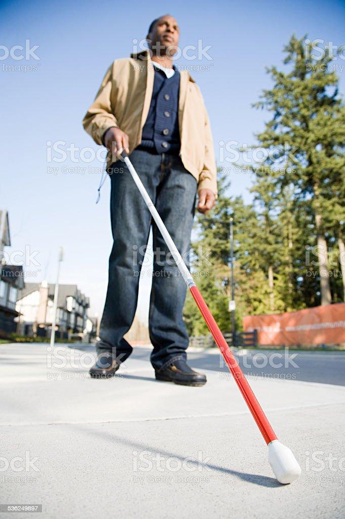 Blind man using a walking stick stock photo