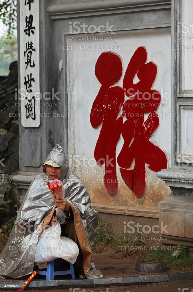 Blind old man selling incense in front of a temple stock photo