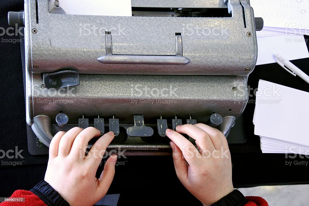 Blind person typing on a braille typing machine stock photo