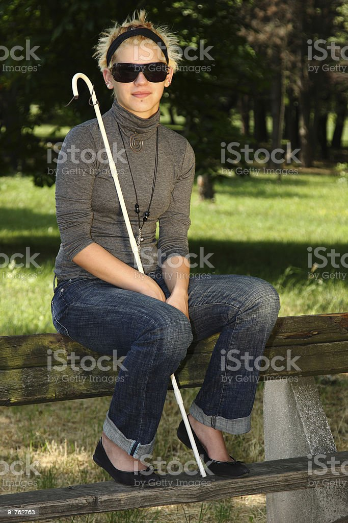 blind woman sitting on a park stock photo