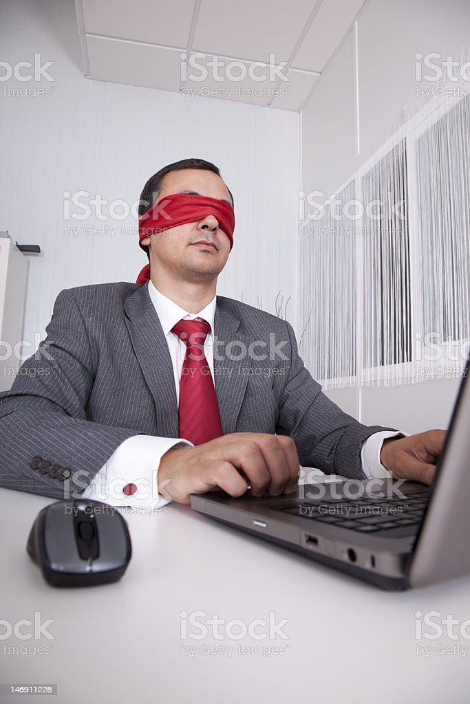Blindfold businessman working with his laptop royalty-free stock photo