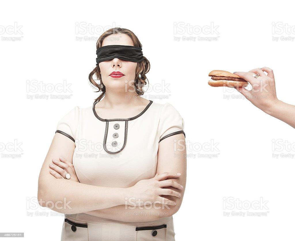 Blindfold plus size woman temptating with hamburger royalty-free stock photo