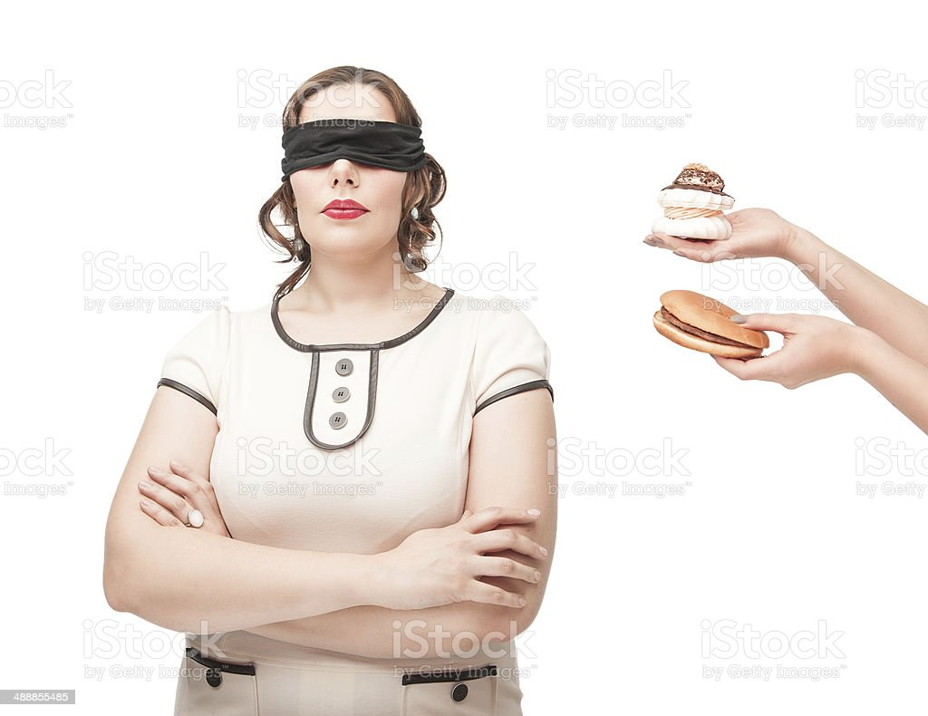 Blindfold plus size woman temptating with junk food stock photo