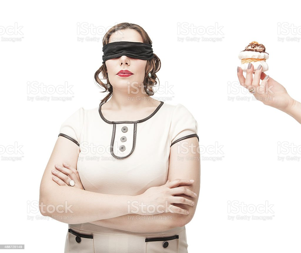 Blindfold plus size woman temptating with pastry stock photo